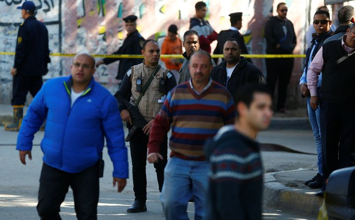 Plain clothes police officers stand guard at the scene of a bomb blast in Giza Al Haram Street on the outskirts of Cairo, Egy