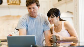 USA, Utah, couple using laptop in kitchen