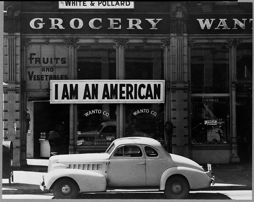 "A large sign reading ""I am an American"" placed in the window of a store on the day after Pearl Harbor. The store was clo"