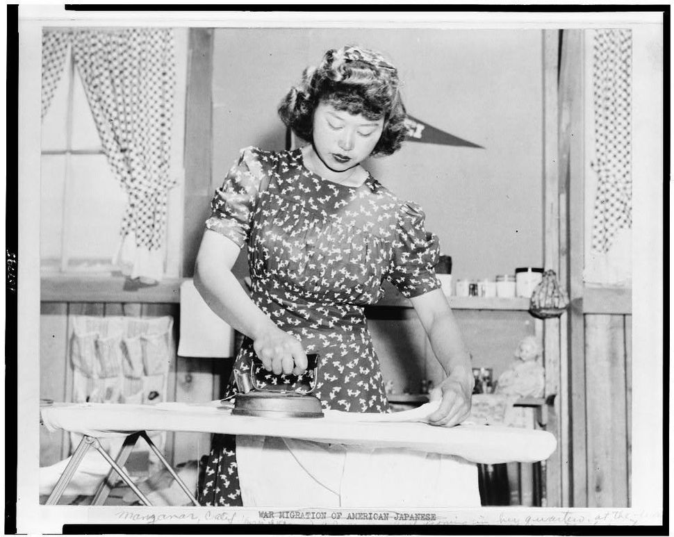 """Ester Naite, an office worker from Los Angeles, is shown operating an electric iron in her quarters at a """"War Relocation Auth"""