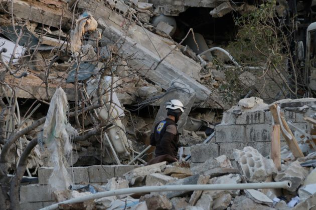 A rescue worker searches the debris of a collapsed hospital in Idlib Province on Feb. 15,