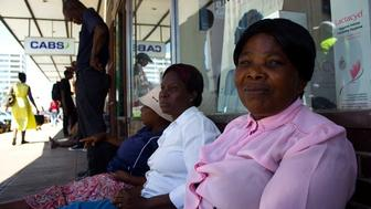 Siphiwe Esiphakathi sits with other women in a queue outside a bank in Bulawayo Zimbabwe hoping to get access to their cash For many women waiting for hours to get money in the midst of the countrys cash shortage means skipping doctors appointments or essential treatments