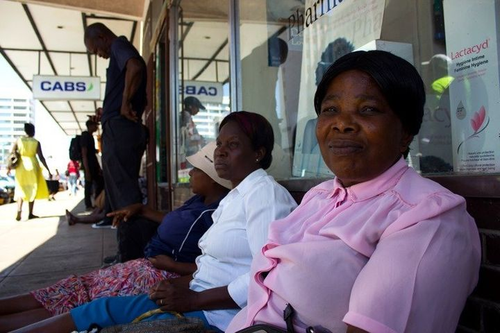 Siphiwe Esiphakathi sits with other women in a queue outside a bank in Bulawayo, Zimbabwe, hoping to get access to their cash