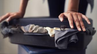 A woman trying to close an over-full suitcase