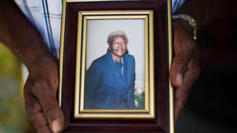 Walter Jackson holds a photo of his mother Susie Jackson, one of the nine people killed in Wednesday's shooting at Emanuel AME Church, as he stands on his front porch Friday, June 19, 2015, in Charleston, S.C. (AP Photo/David Goldman)