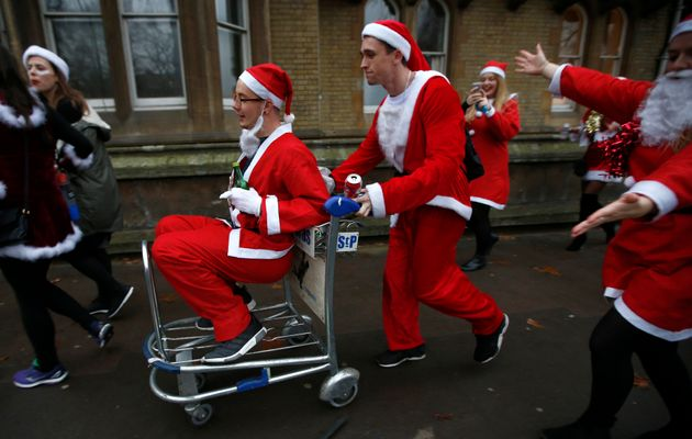 Revellers dressed as Santa push one another in a