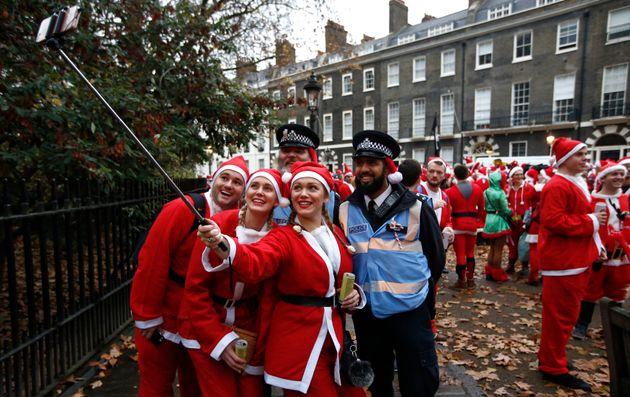 Groups dressed as Santas take a selfie with