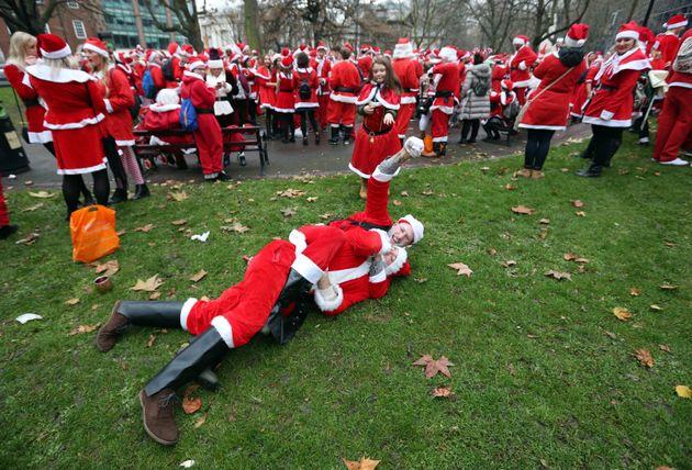 Revellers dressed in Santa suits wrestle outside