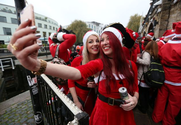 Two revellers dressed in Santa suits take a selfie before setting off fromCamden in the Santacon...