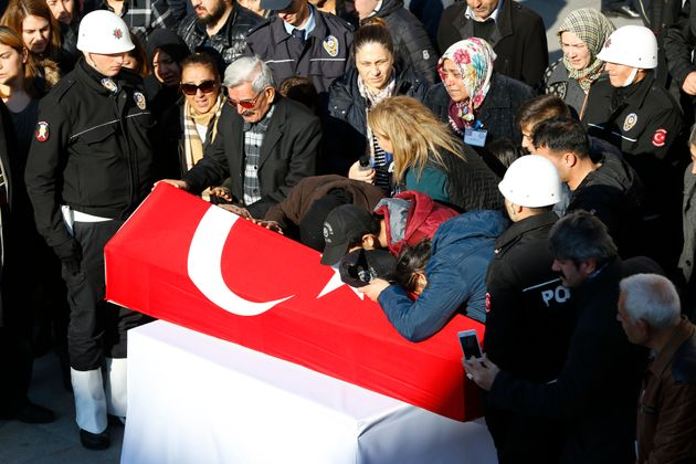 Relatives mourn next to a coffin of a Turkish police officer killed in Saturday's blasts in Istanbul,...