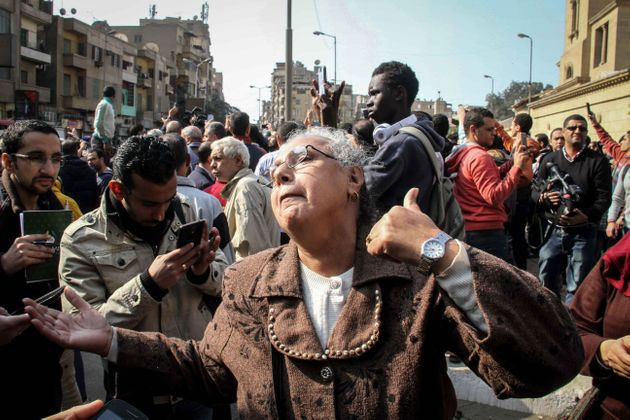 People react at site after an explosion at Saint Mark's Coptic Orthodox Cathedral in Cairo, Egypt on...