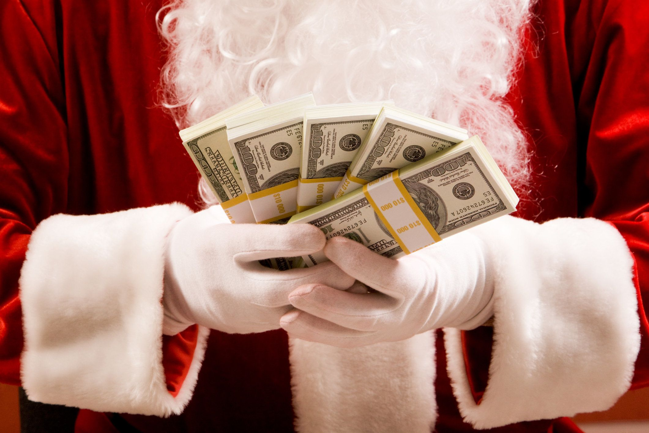 Close-up of Santa's hands with stacks of dollar banknotes