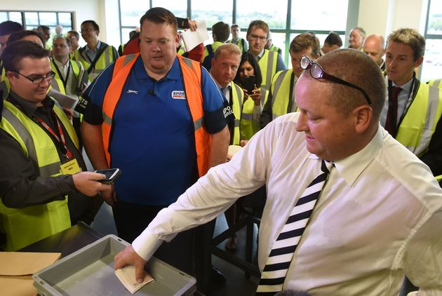 Sports Direct CEO Mike Ashley emptying wads of fifty pound notes during a PR tour of a