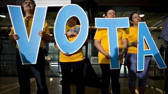 Attendees hold letters reading 'Vote' in Spanish during a campaign event with Tim Kaine, 2016 Democratic vice presidential nominee, in Phoenix, Arizona, U.S., on Thursday, Nov. 3, 2016. Five days from the U.S. presidential election, polls released Thursday showed the race narrowing, with Democrat Hillary Clinton holding on to a slim lead over Republican Donald Trump. Photographer: Daniel Acker/Bloomberg via Getty Images