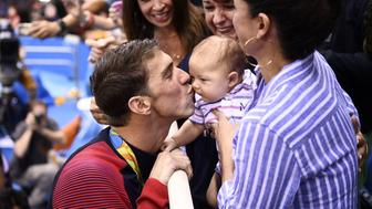 USA's Michael Phelps (L) kisses his son Boomer next to his partner Nicole Johnson (R) and mother Deborah (C) after he won the Men's 200m Butterfly Final during the swimming event at the Rio 2016 Olympic Games at the Olympic Aquatics Stadium in Rio de Janeiro on August 9, 2016.   / AFP / Martin BUREAU        (Photo credit should read MARTIN BUREAU/AFP/Getty Images)
