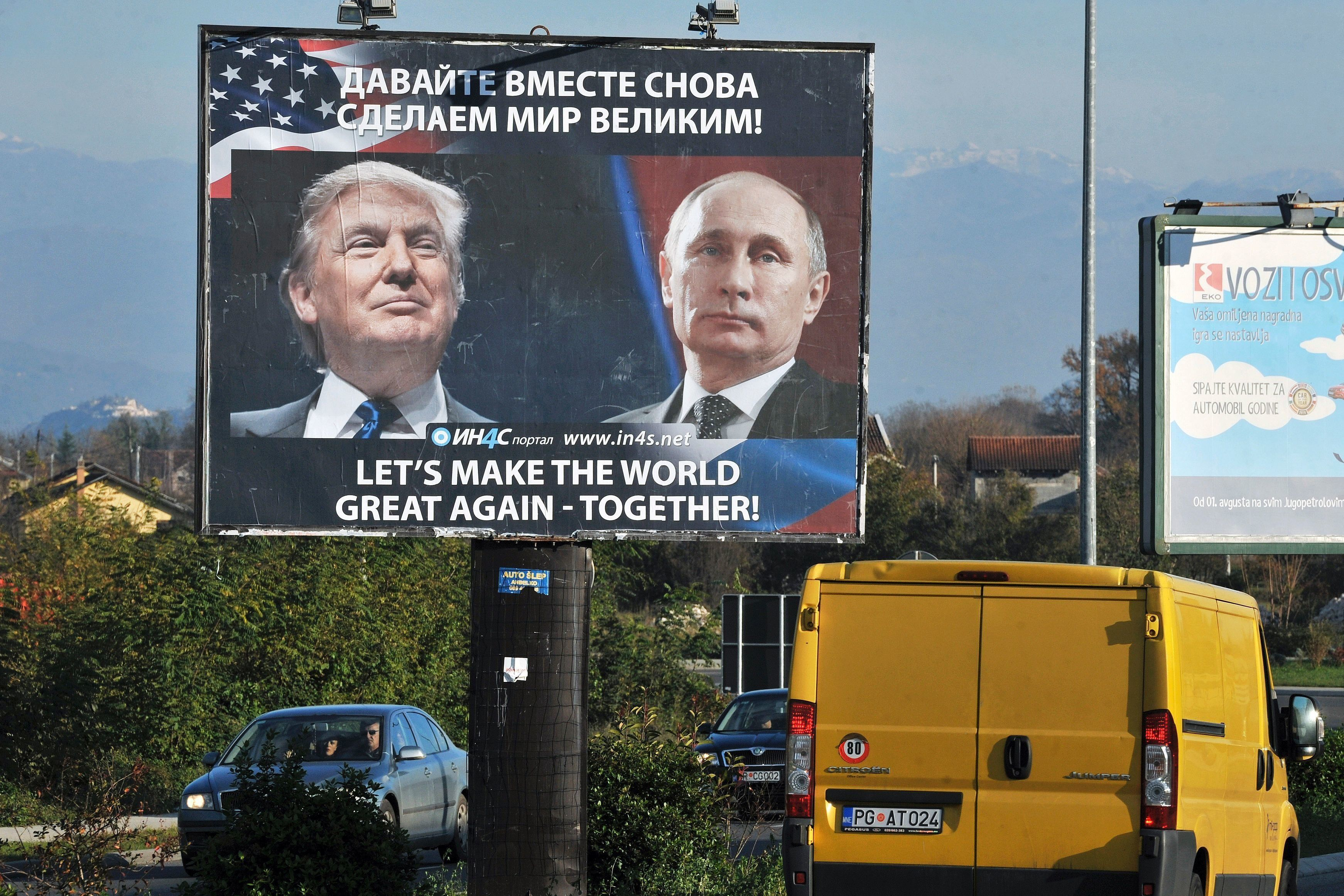 Cars pass by a billboard showing U.S. President-elect Donald Trump and Russian President Vladimir Putin placed by a pro-Serbi