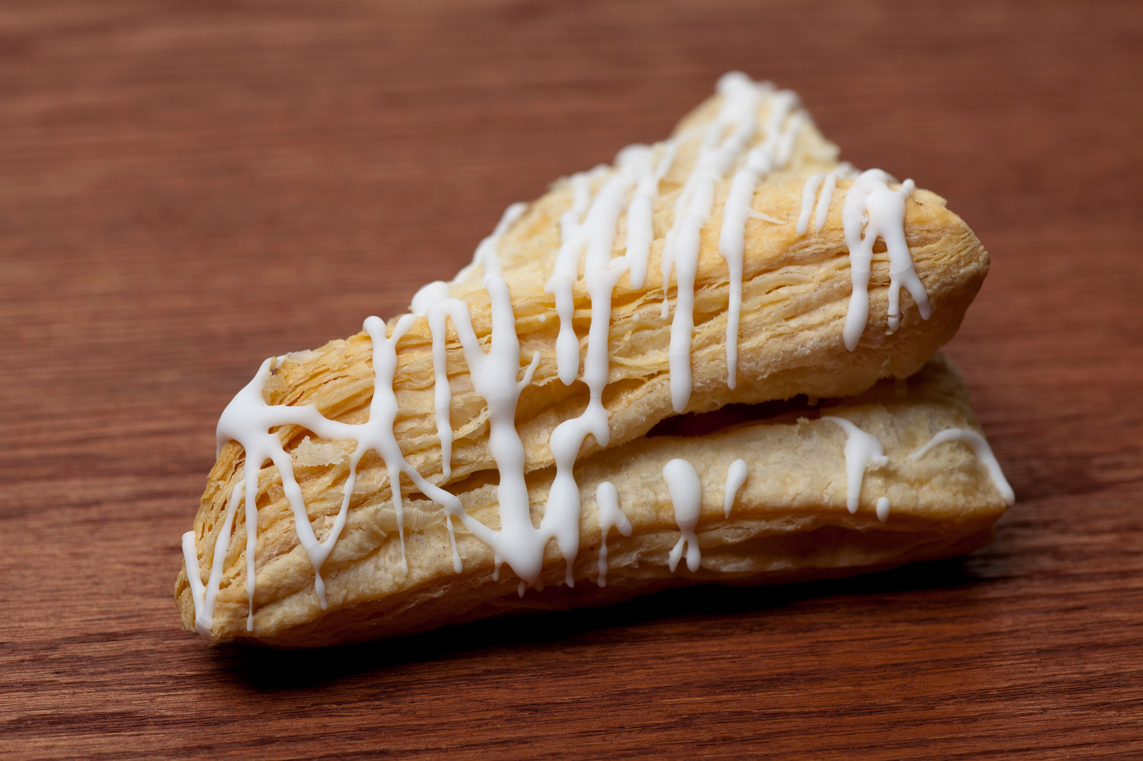 A close up of a fruit turnover on a wood surface. Turnovers are made like croissants with a laminated dough and can have a number of different fruit fillings like apple, blueberry, and peach. They're also topped with icing.