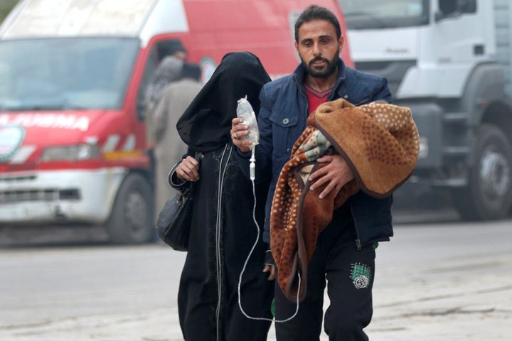 A man carries a child with an IV drip in Aleppo, Syria, on Dec.12, 2016.
