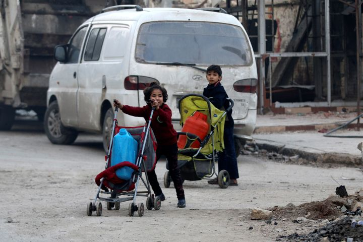 Children push containers in strollers as they flee deeper into the remaining rebel-held areas of Aleppo, Syria December 12, 2