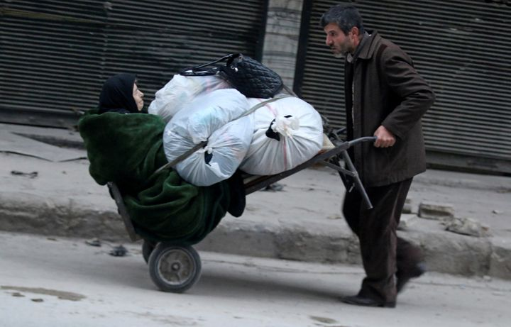 A man pushes a cart carrying an elderly woman and belongings as they flee deeper into the remaining rebel-held areas of Alepp