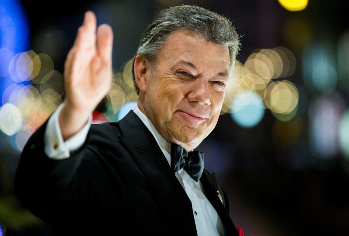 Nobel Peace Prize laureate Colombian President Juan Manuel Santos reacts to the torchlight parade from the balcony of the Gra