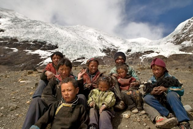 Local children sitin front of one of the glaciers on the Tibetan