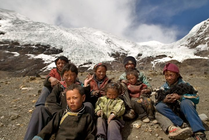 Local children sit in front of one of the glaciers on the Tibetan plateau.