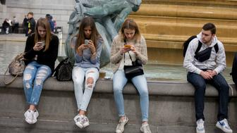 Three teenage girls are lost in the world of smartphone apps and messaging, in Trafalgar Square. While in a very busy environment in the capital's main square in central London and with the admiring glance of a young man alongside, the teenagers obsessively tweet and message their friends at home, completely unaware of their surroundings, absorbed in the functions of their devices and their young lives. Sitting on the walls of the fountains, they are isolated from each other and the noise around (Photo by In Pictures Ltd./Corbis via Getty Images)