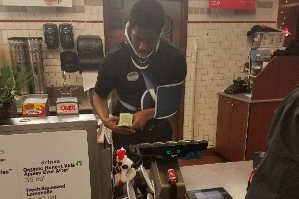 A fundraiser is underway to help a Chick-fil-a cashier who was seen working with a neck brace and sling