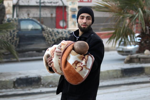 A man carries a child as he flees deeper into the remaining rebel-held areas of