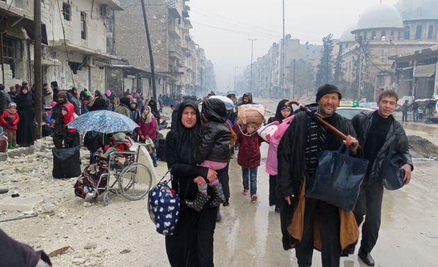 Syrian residents, fleeing violence in the restive Bustan al-Qasr neighbourhood, arrive in Aleppo's Fardos