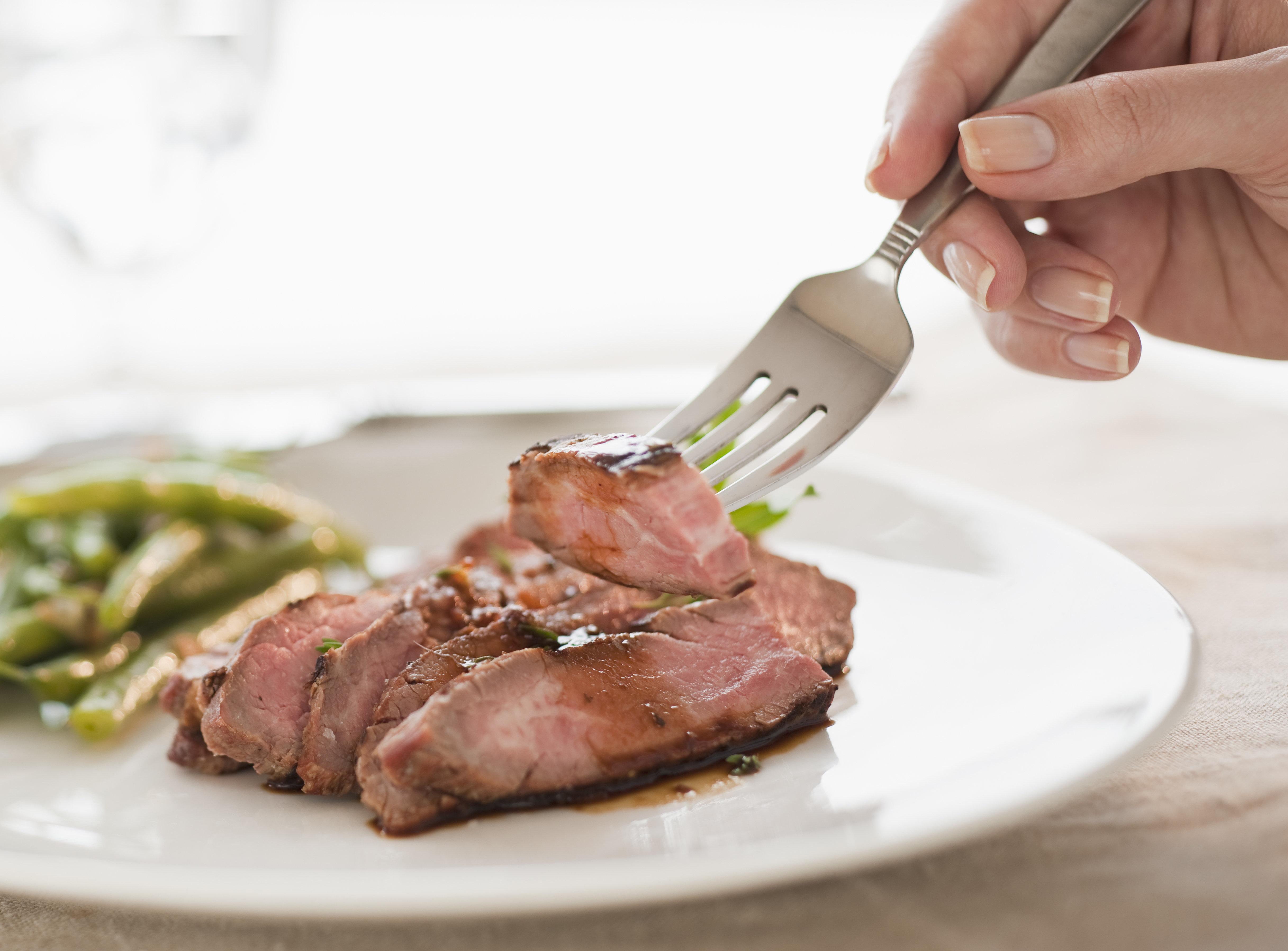 female hands holding forkful of sliced sirloin, gravy, green beans