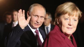 BERLIN, GERMANY - OCTOBER 19:  Russian President Vladimir Putin waves as he walks with German Chancellor Angela Merkel upon his arrival to discuss the Ukrainian peace process at the Chancellery on October 19, 2016 in Berlin, Germany. The leaders of Russia, Ukraine, France and Germany, known as the Normandy Four, are meeting to discuss implementation of the peace plan known as the Minsk Protocol, a roadmap for resolving the conflict in Ukraine after Russian forces invaded in 2014 and annexed the peninsula of Crimea. The United States has threatened renewed sanctions on Russia if the country did not either implement the plan in the coming months or arrive at a plan on how to do so.  (Photo by Sean Gallup/Getty Images)