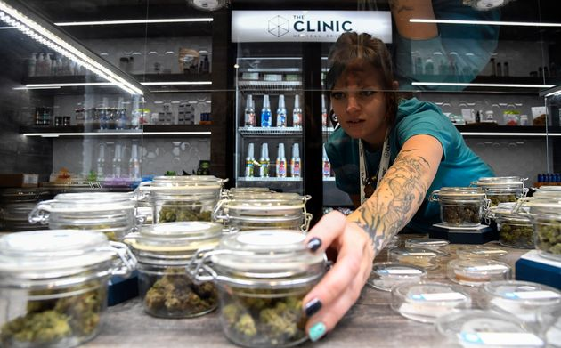 Holly Kinnel straightens out the display case at the new location for The Clinic, a marijuana retailer...