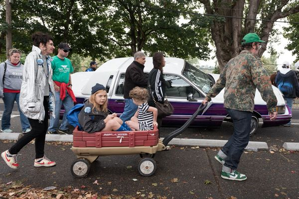 Following the parade march, Christian pulls the family past a Fiestas Patrias lowrider show.