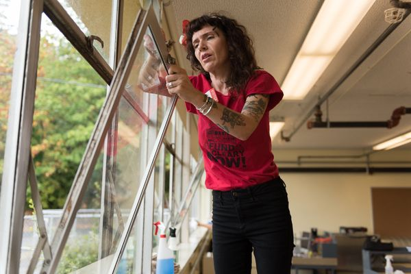 """Shawna window washes in the shop classroom. Her """"Fund McCleary Now"""" T-shirt (which she produced with fellow advocate Carolyn"""