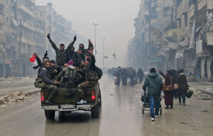 Syrian pro-regime fighters victoriously throw their hands in the air as they drive past residents fleeing violence in th
