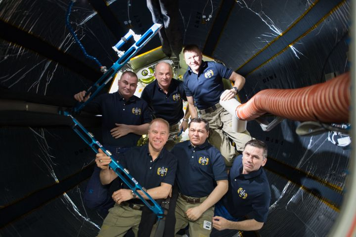 The crew of Expedition 47 poses inside BEAM, the Bigelow Expandable Activity Module.