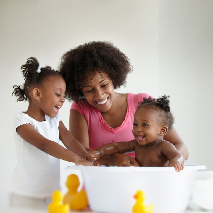 Mother And Daughter Giving Baby Girl A Bath LWA via Getty Images