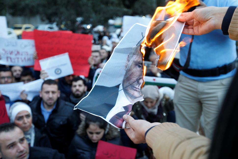Protesters in front of the Russian Embassy in Amman, Jordan, burn a picture of Russian President Vladimir Putin during a