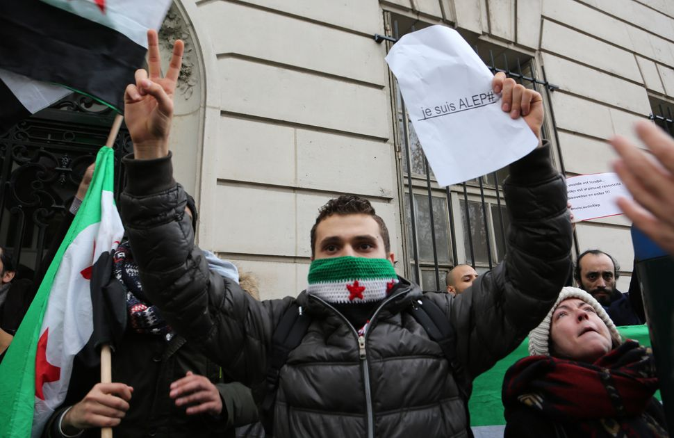 "A man holds a sign saying ""I am Aleppo"" during a protest outside of the Russian Embassy in Paris on Dec. 13, 2016."