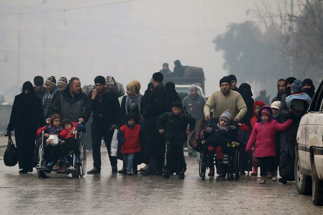 People walk as they flee deeper into the remaining rebel-held areas of Aleppo, Syria December 13,