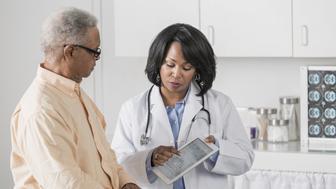 African American doctor showing patient digital tablet