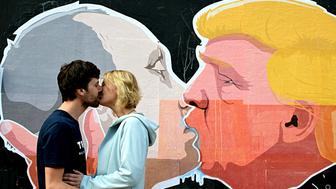 VILNIUS, LITHUANIA - MAY 19: A couple kisses in front of mural depicting Russian President Vladimir Putin and Republican presidential candidate Donald Trump, on the walls of a barbecue bar 'Keule Ruke' on May 19, 2016 in Vilnius, Lithuania.  PHOTOGRAPH BY News Bridgepix / Barcroft Images   London-T:+44 207 033 1031 E:hello@barcroftmedia.com - New York-T:+1 212 796 2458 E:hello@barcroftusa.com - New Delhi-T:+91 11 4053 2429 E:hello@barcroftindia.com www.barcroftmedia.com (Photo credit should read News Bridgepix / Barcroft Images / Barcroft Media via Getty Images)