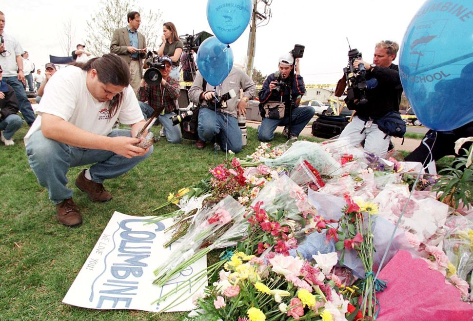 People and press gather at a memorial outside Columbine High School, the scene of a mass shooting on April 20, 1999.