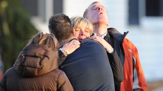 Unidentified people embrace on December 14, 2012 at the aftermath of  a school shooting at a Connecticut elementary school  that brought police swarming into the leafy neighborhood, while other area schools were put under lock-down, police and local media said. Local media quoted  that the gunman had died at the Sandy Hook Elementary School in Newtown, Connecticut, northeast of New York City.  At least 27 people, including 18 children, were killed on Friday when at least one shooter opened fire at an elementary school in Newtown, Connecticut, CBS News reported, citing unnamed officials. AFP PHOTO/DON EMMERT / AFP / DON EMMERT        (Photo credit should read DON EMMERT/AFP/Getty Images)