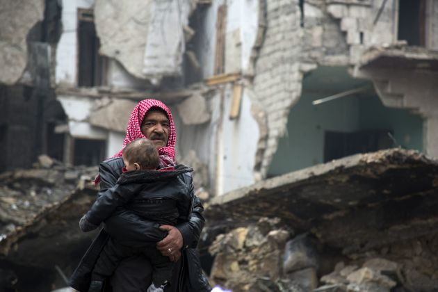 A Syrian man carries a child through the ruins of