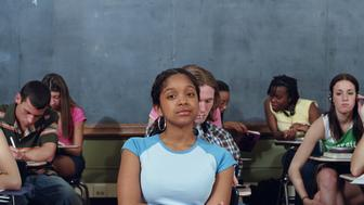 Teenagers (15-18) in classroom, girl with arms folded, portrait