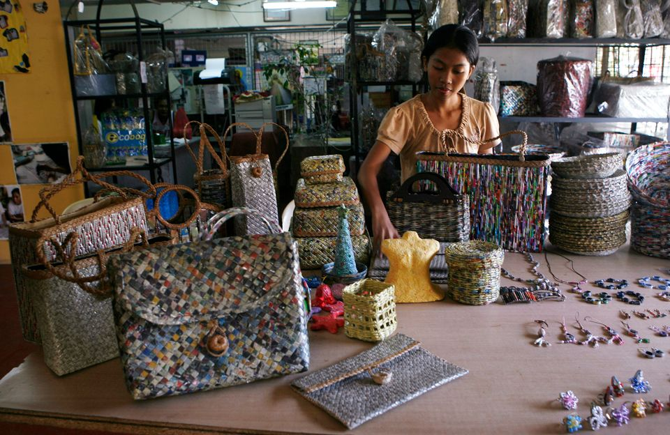 One of the slum dwellers displays handbags and shoulder bags, made from newspapers, magazines and telephone...