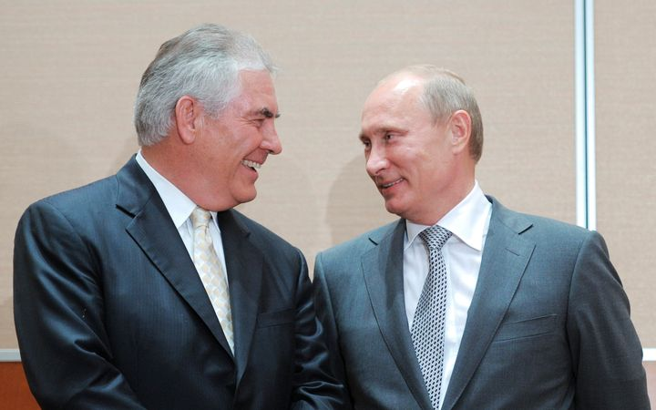 Russian Prime Minister Vladimir Putin (R) speaks with Exxon CEO Rex Tillerson at a signing ceremony in the Black Sea resort o